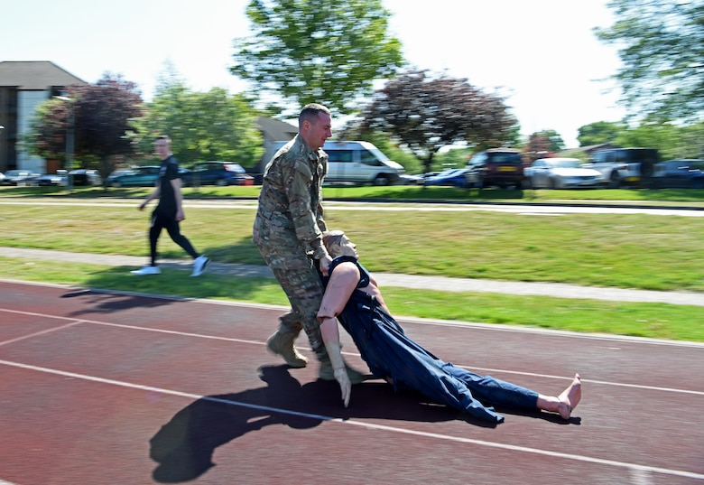 """U.S. Air Force 1st Lt. Ricky Sizemore, 100th Security Forces Squadron flight commander, drags a casualty dummy during the 48th Security Forces Squadron's """"Spartan Race,"""" which is a part of National Police Week at RAF Lakenheath, England, May 14, 2019. National Police Week is a chance for all law enforcement officials to pay respects to the officers who came before them, and also gives the base community the opportunity to support the force as well. (U.S. Air Force photo by Airman 1st Class Brandon Esau)"""