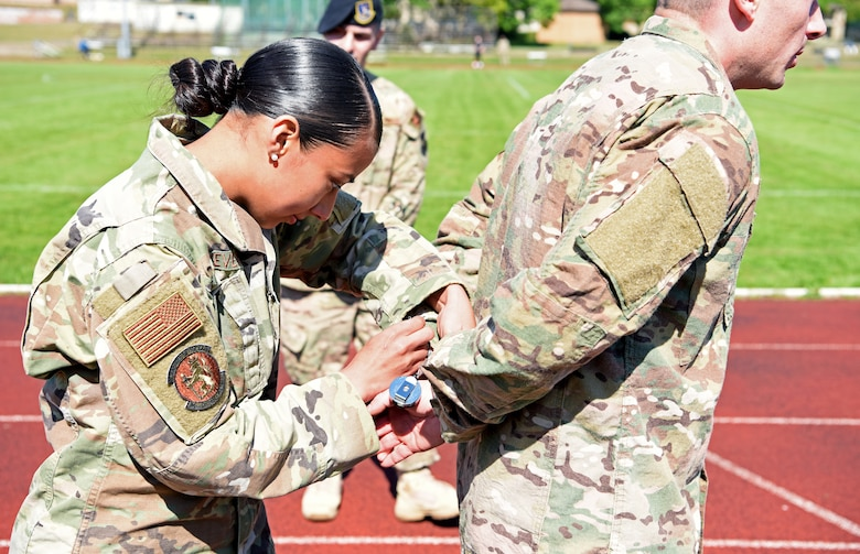 """U.S. Air Force Airman 1st Class Maria Stevens, 100th Security Forces Squadron member, handcuffs 1st Lt. Ricky Sizemore, 100th SFS flight commander, during the 48th Security Forces Squadron's """"Spartan Race,"""" which is a part of National Police Week at RAF Lakenheath, England, May 14, 2019. This commemorative week began in 1962 when U.S. President John F. Kennedy signed a proclamation that designated May 15 as """"Peace Officers Memorial Day,"""" and the week in which that date falls as National Police Week. (U.S. Air Force photo by Airman 1st Class Brandon Esau)"""