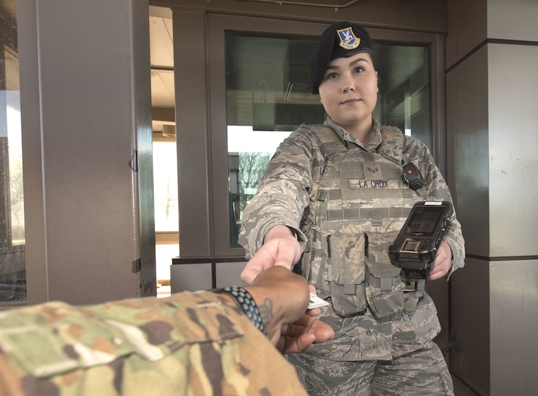 Airman 1st Class Stevie La Croix, 50th Security Forces Squadron response force patrolman, verifies the credentials of an individual seeking to gain entry to the installation's North Gate at Schriever Air Force Base, Colorado, May 15, 2019. As a response force patrolman, La Croix is one the base's first lines of defense to disasters either natural or man-made. In this role, Airmen like La Croix are fulfilling the 50th Space Wing priority of successfully and innovatively executing operations. (U.S. Air Force photo by Staff Sgt. Matthew Coleman-Foster)