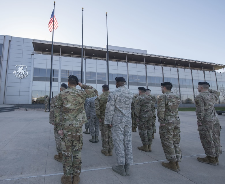 50th Security Force Squadron members render a salute while in formation for Police Week reveille in front of Building 210 at Schriever Air Force Base, Colorado, May 13, 2019. 50th SFS planned the reveille, a 5K run, walk, ruck march and a weapons display in observance of the week.  (U.S. Air Force photo by Staff Sgt. Matthew Coleman-Foster)