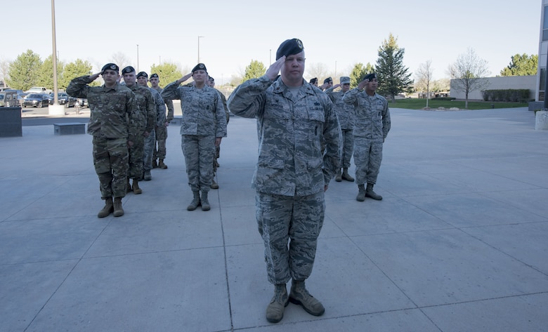Maj. Adam Morgan, 50th Security Forces Squadron commander, leads his formation in reveille in honor of Police Week in front of Building 210 at Schriever Air Force Base, Colorado, May 13, 2019. National Police Week gives special recognition to all law enforcement officers who have dedicated and given their lives to protecting their communities. (U.S. Air Force photo by Staff Sgt. Matthew Coleman-Foster)