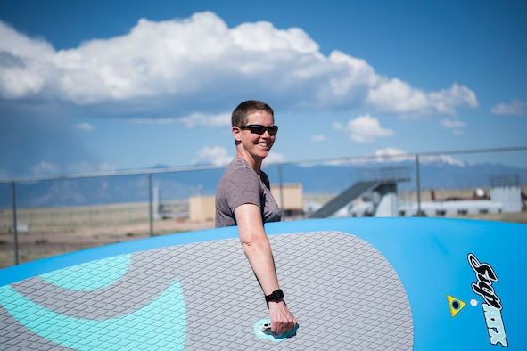 Juli Yim, 50th Force Support Squadron director of outdoor recreation, holds one of the new stand-up paddleboards purchased for outdoor recreation at Schriever Air Force Base, Colorado, May 14, 2019. The 50th FSS also purchased new campers, bounce houses and replaced old equipment. (U.S. Air Force photo by Airman Jonathan Whitely)