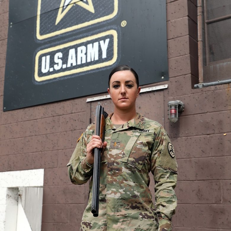 Female soldier in camouflage uniform poses with her shotgun.