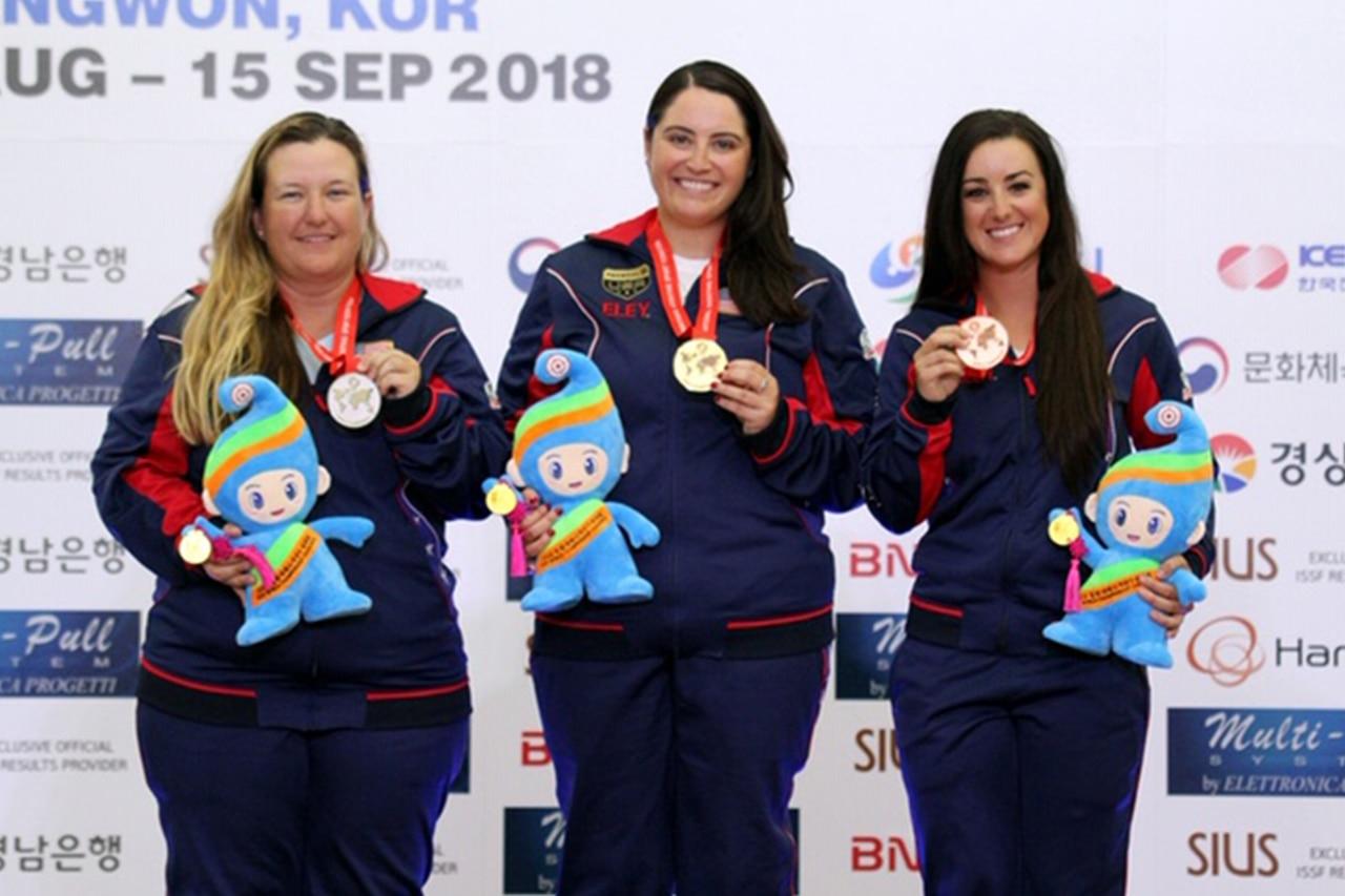 Three women stand on a winner's podium.