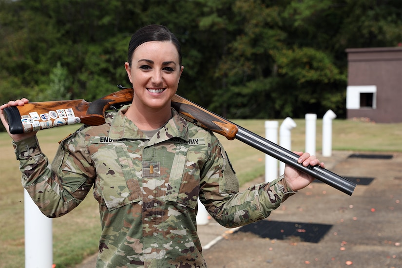 Female soldier in camouflage uniform poses with her shotgun on her back.