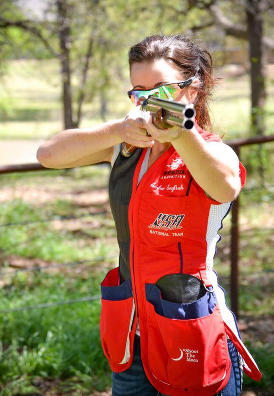 A woman aims a shotgun.