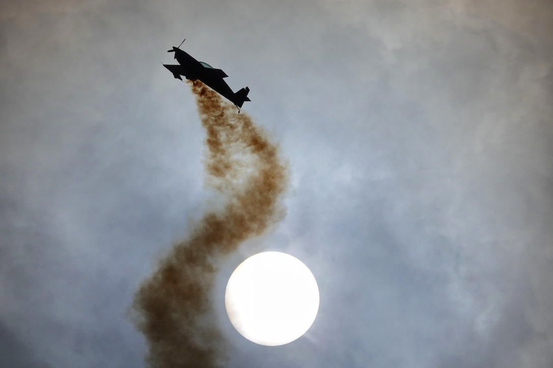 A small plane flies through a cloudy sky leaving a trail of brown smoke circling one side of the sun.