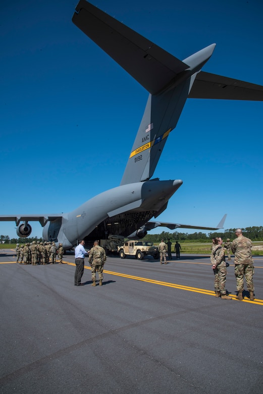 Citizen Airman of the 300th Airlift Squadron Joint Base Charleston, S.C. and Soldiers from the 414th Signal Company at Fort Stewart, Georgia, prepare to load a humvee and radar system on to a C-17 Globemaster III, May 14, 2019, at Wright Army Airfield. The humvee and radar system were loaded on to the C-17 as part of an Expeditionary Deployment Readiness Exercise. (U.S. Air Force photo by Senior Airman William Brugge)