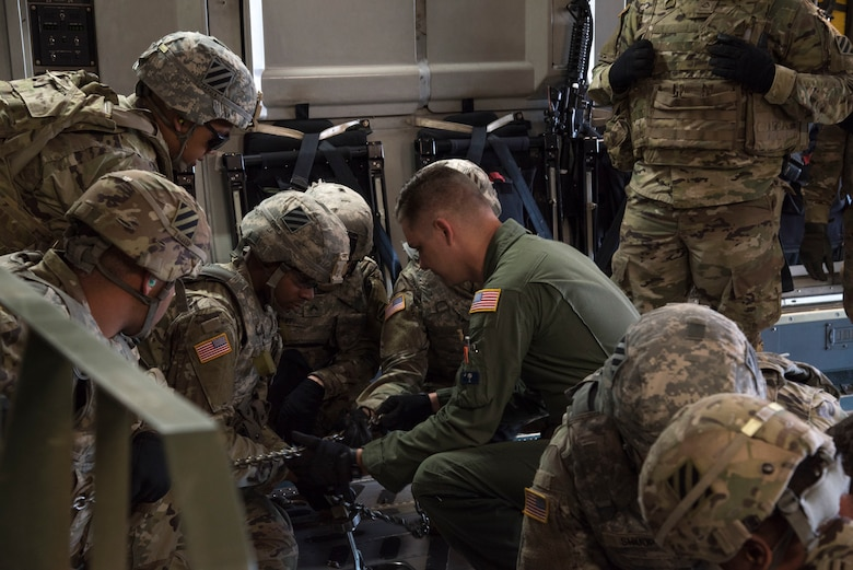 U. S. Air Force Senior Airman Branden Burkhart, loadmaster with the 300th Airlift Squadron Joint Base Charleston, S.C., teaches soldiers with the 414th Signal Company from Fort Stewart, Georgia how to secure equipment on a C-17 Globemaster III May 14, 2019, at Wright Army Airfield. The soldiers trained to be ready during an Expeditionary Deployment Readiness Exercise.(U.S. Air Force photo by Senior Airman William Brugge)