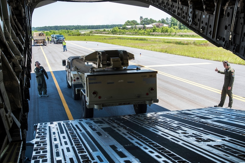 U. S. Air Force Tech. Sgt. Albert Pempsell and Senior Airman Branden Burkhart, loadmasters with the 300th Airlift Squadron Joint Base Charleston, S.C., help load equipment on to a C-17 Globemaster III May 14, 2019, at Wright Army Airfield. The equipment was loaded on to the aircraft for an Expeditionary Deployment Readiness Exercise to help bolster combat readiness. (U.S. Air Force photo by Senior Airman William Brugge)