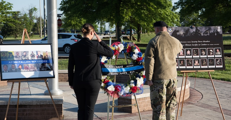 A defender with the 509th Security Forces Squadron, right, and an Air Force Office of Special Investigation agent salute the wreath they placed during the National Police Week opening ceremony May 13, 2019, at Whiteman Air Force Base, Missouri. During Police Week, members of both Air Force law enforcement agencies commemorate their fallen wingmen. (U.S. Air Force Photo by Airman Parker J. McCauley)