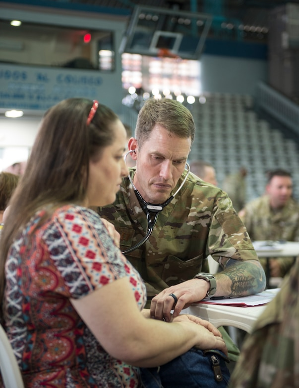 U.S. Air Force Capt. Chad Macheel, a medical provider with the 133rd Medical Group, checks the pulse of patients in Lares, Puerto Rico, April 30, 2019.