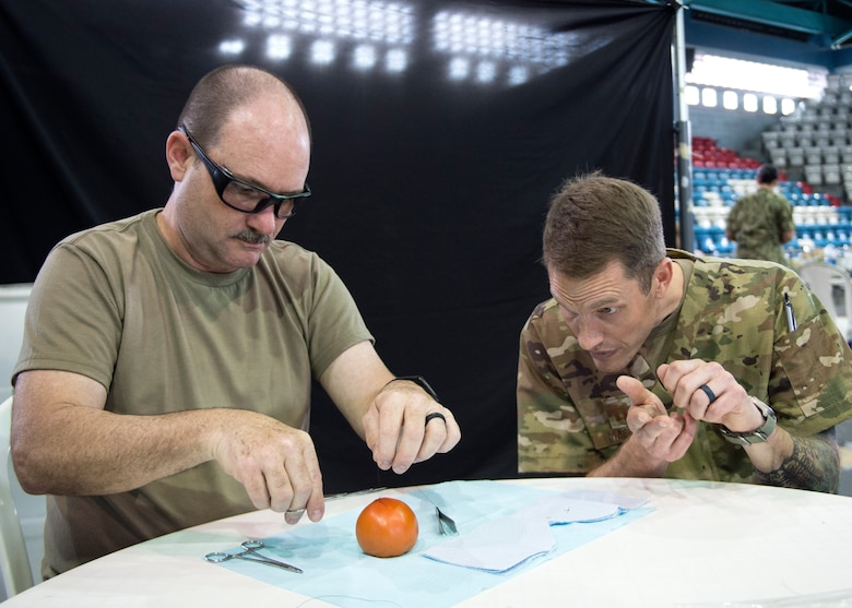 U.S. Army Sgt. 1st Class Robert Abbott, an optometrist technician with the 335th Area Support Medical Company, 49th Multifunctional Medical Battalion, learns how to suture from U.S. Air Force Capt. Chad Macheel, a medical provider with the 133rd Medical Group, in Lares, Puerto Rico, May 2, 2019.