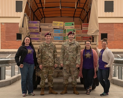 Three Girl Scouts and two military members stand in front of truck filled with cookies