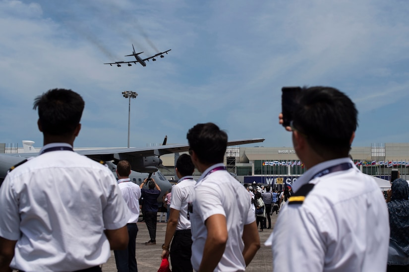 A bomber flies over a crowd of uniformed personnel.