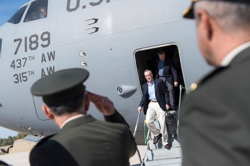 Men in uniform salute a man in civilian clothes exiting an airplane.