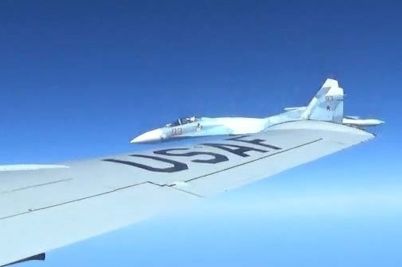 A jet flies close to another aircraft's wing.