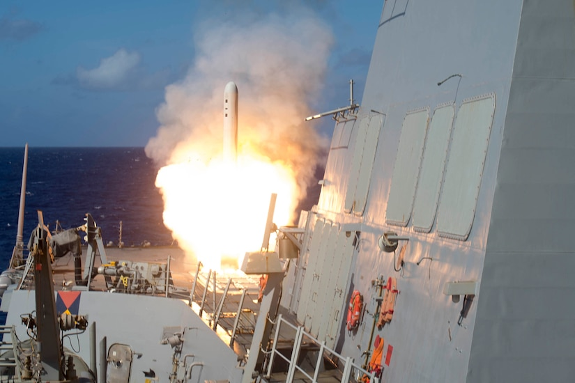 A missile launches from a ship at sea.