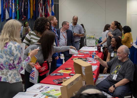 women and men visit vendor tables during the 20th Health and Safety Expo in the HQC Café, May 14.