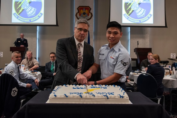 Frederick Wirsing, Air Mobility Command chief weather operations and plans branch, and U.S. Air Force Airman 1st Class Arjay Canonizado, 15th Operational Weather Squadron forecaster, cut the cake at the 15th OWS 20th anniversary dinner, Feb. 12, 2019, at Scott Air Force Base, Ill. During its 77 years, the 15th OWS has been located in six states and four countries across three different continents. It has spent the last 20 years assigned to Scott. (U.S. Air Force photo by Senior Airman Daniel Garcia)