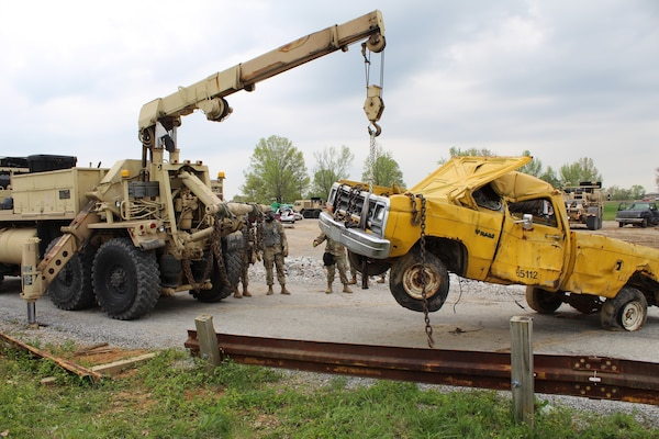 Soldiers from 104th Engineer Construction Company, Task Force Ops, Joint Task Force Civil Support (JTFCS), move damaged vehicles from a road to clear the way for search and rescue teams during Exercise Guardian Response at Muscatatuck, Ind., 30 April, 2019. When directed, JTFCS provides command and control of the 5,200-person Defense Chemical Biological Radiological Nuclear(CBRN) Response Force (DCRF) during a catastrophic crisis in support of civil authorities and the lead federal agency. Vibrant Response/Guardian Response is an annual, combined Command Post Exercise and Field Training Exercise which validates the ability of the DCRF forces to conduct the CBRN Response mission. (U.S. Army photo by 2nd Lt. Corey Maisch/released)