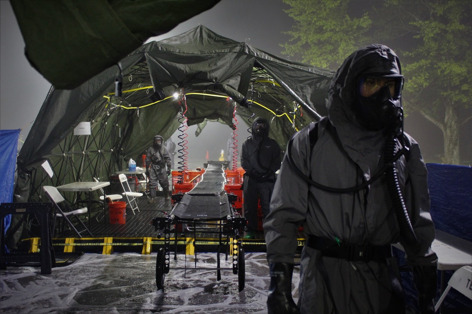 Soldiers from 181st Chemical Company (Hazard Response), Task Force Ops, Joint Task Force Civil Support (JTFCS), are prepared for role-players to come through their Mass Casualty Decontamination line at Exercise Guardian Response at Muscatatuck Urban Training Center, May 4, 2019. When directed, JTFCS provides command and control of the 5,200-person Defense Chemical Biological Radiological Nuclear (CBRN) Response Force (DCRF) during a catastrophic crisis in support of civil authorities and the lead federal agency. Vibrant Response/Guardian Response is an annual, combined Command Post Exercise and Field Training Exercise which validates the ability of the DCRF forces to conduct the CBRN Response mission. (U.S. Army photo by 2nd Lt. Corey Maisch/released)