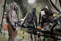 Soldiers from 546th Area Support Medical Company and 181st Chemical Company (Hazard Response), Task Force Ops, Joint Task Force Civil Support (JTFCS) bring a simulated patient through the Mass Casualty Decontamination line during Exercise Guardian Response at Muscatatuck Urban Training Center, May 4, 2019. When directed, JTFCS provides command and control of the 5,200-person Defense Chemical Biological Radiological Nuclear (CBRN) Response Force (DCRF) during a catastrophic crisis in support of civil authorities and the lead federal agency. Vibrant Response/Guardian Response is an annual, combined Command Post Exercise and Field Training Exercise which validates the ability of the DCRF forces to conduct the CBRN Response mission. (U.S. Army photo by 2nd Lt. Corey Maisch/released)