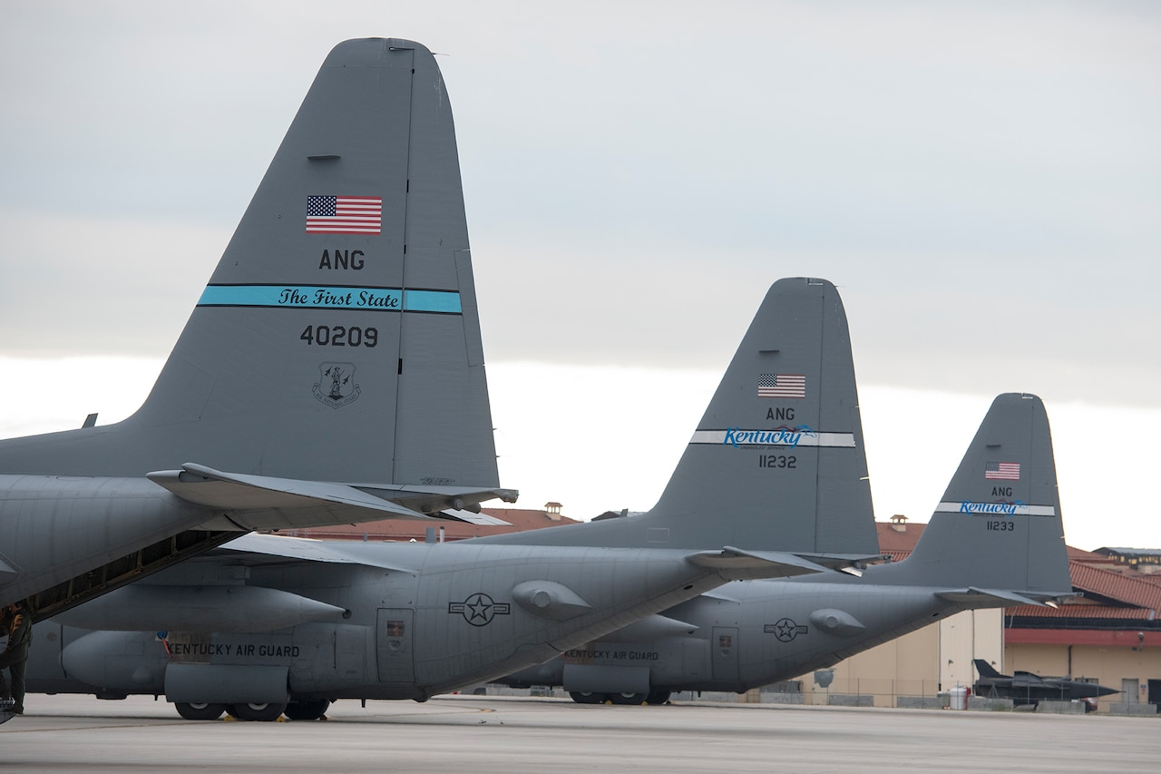 Tails of three C-130 cargo aircraft on a flight line.