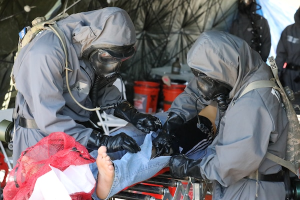 U.S. Army Soldiers of the 66th Military Police Company conduct simulated, urban search and rescue operations in an area with chemical, biological, radiological or nuclear contamination during Guardian Response 19 at Muscatacuck Urban Training Center, Ind., May 5, 2019. Civilian role players acted as inhabitants of the local area, and provided the soldiers with realistic, real world training during the decontamination procedures. (U.S. Army Reserve photos by Sgt. Philip Scaringi/released)