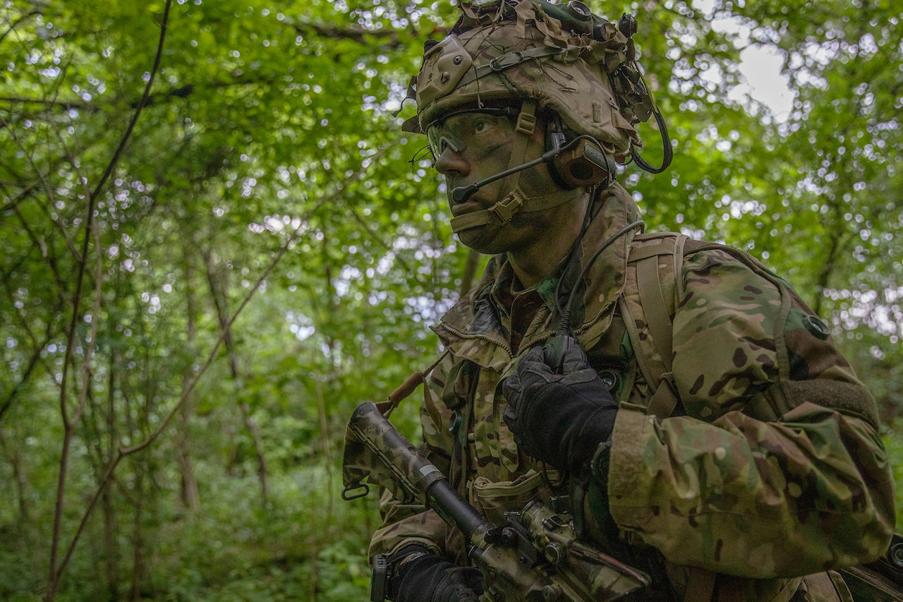 Soldier in camouflage uniform and face paint walks in a wooded area.