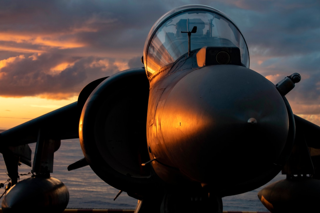 Sunlight reflects off a fighter jet as it waits on a flight deck with the ocean in the background.