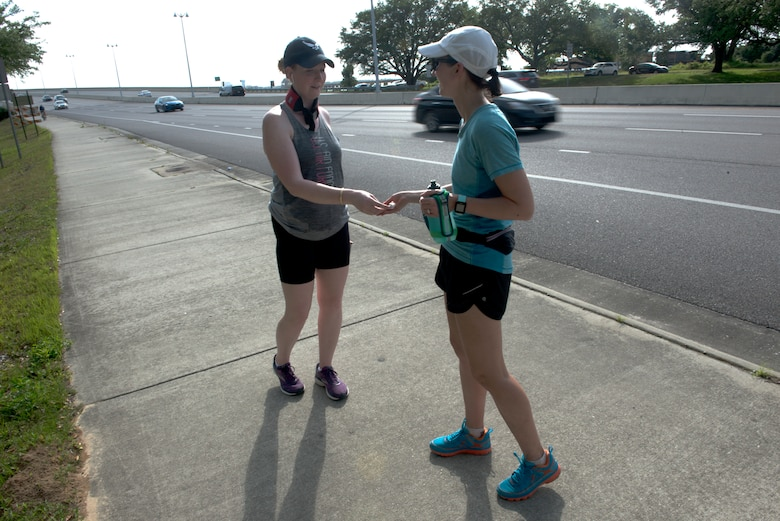"U.S. Air Force Capt. Kelly Hiser, 335th Training Squadron force support officer, hands a combat controller coin to another team member during the Crawfish Relay at Biloxi, Mississippi, May 3, 2019. The relay team, ""Unicorn of the Sea,"" accepted the challenge of the Crawfish Relay to not only push themselves, but to honor two special tactics Airmen killed in action, U.S. Air Force Master Sgt. John Chapman and U.S. Air Force Staff Sgt. Dylan Elchin. The team carried two combat controller coins to symbolize them and handed them off at each checkpoint. (U.S. Air Force photo by Airman Seth Haddix)"