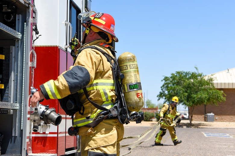 Firefighters from the west valley prepare to lay hose for a joint training exercise May 3, 2019, at Luke Air Force Base, Ariz. The multi-company standard training focused on meeting and excelling in the benchmarks of consistency in fire operations and stretching hose lines to upper levels of buildings. (U.S. Air Force photo by Airman 1st Class Zoie Cox)