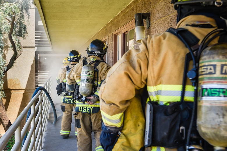 A line of firefighters prepare to enter a room during a joint training exercise May 3, 2019, at Luke Air Force Base, Ariz. The Luke AFB Fire Department responds to emergencies in the local community while local fire departments respond to emergency calls on base. Multi-company standard trainings such as these help firefighters practice basic operating procedures together so they can be effectively used in real world situations. (U.S. Air Force photo by Airman 1st Class Zoie Cox)