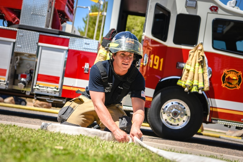 An Arizona Fire Medical Authority firefighter rolls a hose during a joint training exercise May 3, 2019, at Luke Air Force Base, Ariz. The multi-company standard training focused on meeting and excelling in the benchmarks of consistency in fire operations and stretching hose lines to upper levels of buildings. (U.S. Air Force photo by Airman 1st Class Zoie Cox)