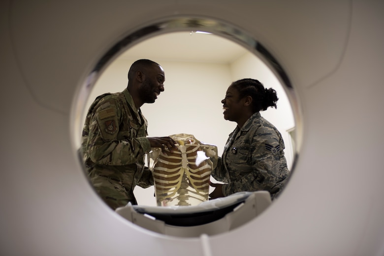 U.S. Air Force Senior Airmen William Gathers III, left, and Shirell Montague, right, both 35th Surgical Operations Squadron radiology technologists, have a laugh at work improving flight morale while inspecting a skeleton model at Misawa Air Base, Japan, April 10, 2019. Medical professionals use human skeletons as learning tools aiding in training by expanding Airmen's knowledge and skills. (U.S. Air Force photo by Senior Airman Collette Brooks)