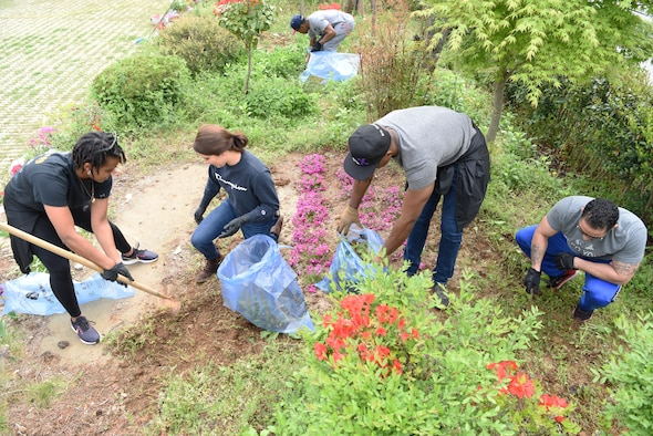 Airmen from various organizations in the 8th Fighter Wing clean a flowerbed outside a women's shelter in Gunsan city April 30, 2019. Over thirty Airmen from the 8th Fighter Wing volunteered their time to help give back to the local community. (U.S. Air Force photo by Staff Sgt. Joshua Edwards)