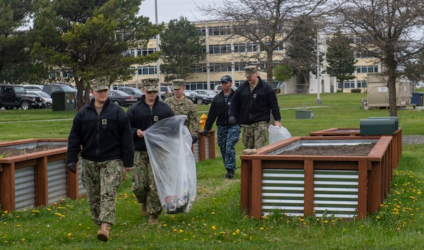 Sailors gather litter around the Liberty Garden gazebo adjacent to the barracks located on Ault Field at Naval Air Station Whidbey Island.
