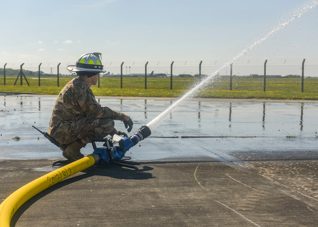 U.S. Air Force Master Sgt. Jeremiah Gates, 100th Civil Engineer Squadron assistant chief of training, sprays water across the pavement at RAF Mildenhall, England, May 15, 2019. The fire department provided water to simulate spilled fuel for the exercise. The fuel spill exercise was conducted to test the base's response and recovery capabilities. (U.S. Air Force photo by Airman 1st Class Joseph Barron)