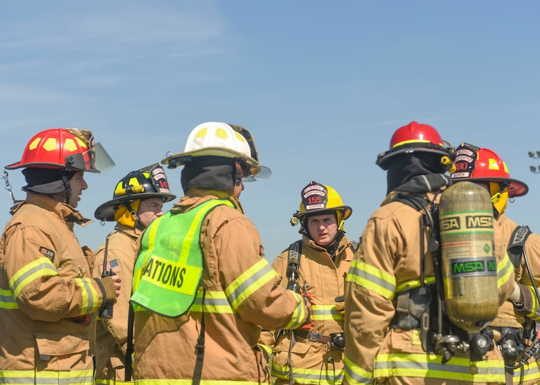 Firefighters discuss the appropriate response to a simulated fuel spill at RAF Mildenhall, England, May 15, 2019. The exercise tested the base's response to 65,000 gallons of spilled fuel. The fuel spill exercise was conducted to test the base's response and recovery capabilities. (U.S. Air Force photo by Airman 1st Class Joseph Barron)