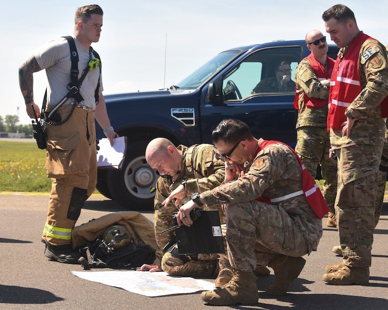 Wing inspection team members and exercise participants from the 100th Air Refueling Wing look over a base map during a fuel spill exercise at RAF Mildenhall, England, May 15, 2019. Exercise participants were evaluated based on their performance during the exercise.  (U.S. Air Force photo by Airman 1st Class Joseph Barron)