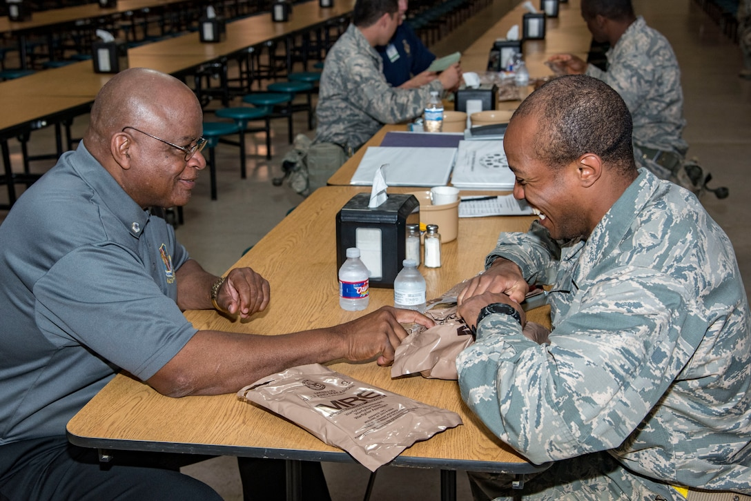 """Air Mobility Command civic leader, Thomas Randall, visits with a trainee during a stop for an MRE lunch at Joint Base San Antonio-Lackland, May 2, 2019.  The civic leaders toured the 37th Training Wing, also known as the """"Gateway Wing,"""" as guests of AMC Cmmander Gen. Maryanne Miller. (U.S. Air Force photo by Traci Howells)"""