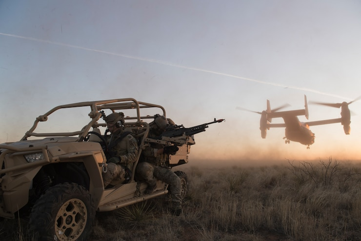 Two Special Tactics Operators cover a twin rotor helicopter as it takes off from a sandy field at twilight.