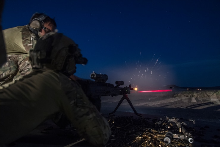 A pair of Special Tactics Operators use a weapon with a laser targeting system to shoot downrange at night.