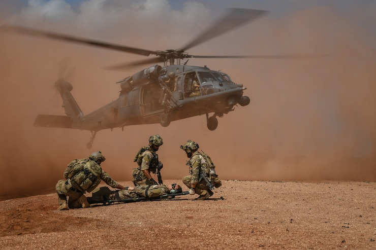 A trio of Special Tactics Operators shield a person on a stretcher from prop wash as the rescue helicopter lands nearby in a desert.