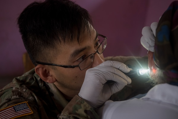 U.S. Army Sgt. Frank Louie-Arishita, Joint Task Force – Bravo Medical Element practical nurse, looks inside a patient's ear as part of a health screening during a Medical Readiness Training Exercise (MEDRETE), May 9, 2019, in El Paraiso, Honduras. Members of JTF-B partnered with the Honduran Military and Ministry of Health to provide health care services for more than 1,300 Honduran citizens; reaching a third of the citizens in the towns of Argelia, Santa Maria and Las Dificultades in the El Paraiso Department. The goal of the mission was to provide the medical staff training in their areas of expertise as well as strengthen partnerships with the Honduran allies. (U.S. Air Force photo by Staff Sgt. Eric Summers Jr.)