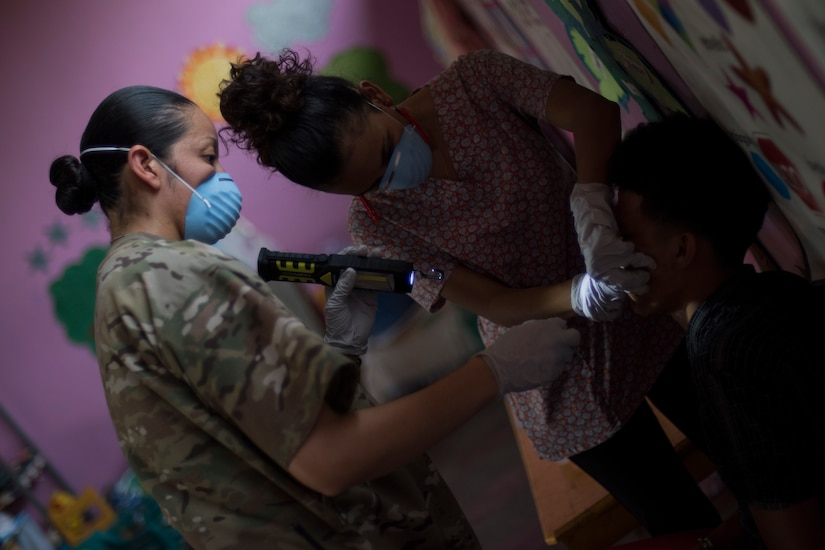 U.S. Army Sgt. Caroline Fuel, Joint Task Force – Bravo Medical Element dental sergeant, holds a light while a Honduran dentist examines a patient during a Medical Readiness Training Exercise (MEDRETE), May 9, 2019, in El Paraiso, Honduras. Members of JTF-B partnered with the Honduran Military and Ministry of Health to provide health care services for more than 1,300 Honduran citizens; reaching a third of the citizens in the towns of Argelia, Santa Maria and Las Dificultades in the El Paraiso Department. The goal of the mission was to provide the medical staff training in their areas of expertise as well as strengthen partnerships with the Honduran allies. (U.S. Air Force photo by Staff Sgt. Eric Summers Jr.)