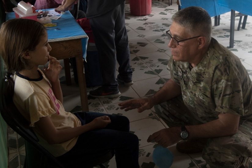 U.S. Army Col. Manuel Iravedra, Joint Task Force – Bravo Medical Element dentist, consoles a young child during a dental examination as part of a Medical Readiness Training Exercise (MEDRETE) May 10, 2019, in El Paraiso, Honduras. Members of JTF-B partnered with the Honduran Military and Ministry of Health to provide health care services for more than 1,300 Honduran citizens; reaching a third of the citizens in the towns of Argelia, Santa Maria and Las Dificultades in the El Paraiso Department. The goal of the mission was to provide the medical staff training in their areas of expertise as well as strengthen partnerships with the Honduran allies. (U.S. Air Force photo by Staff Sgt. Eric Summers Jr.)