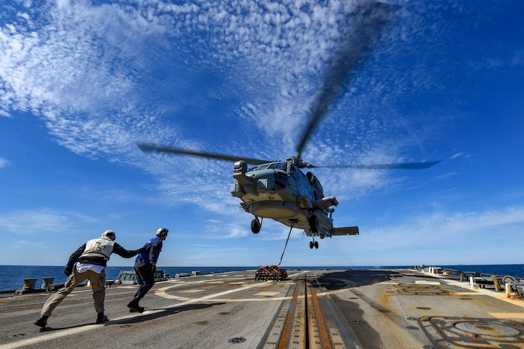 Two sailors walk toward a helicopter as it lands on a military ship.