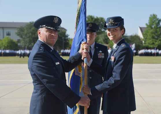 U.S. Air Force Maj. Gen. Timothy Leahy, Second Air Force commander, passes the guidon to Col. Heather Blackwell, 81st Training Wing commander, during a change of command ceremony at the Levitow Training Support Facility drill pad at Keesler Air Force Base, Mississippi, May 16, 2019. The ceremony is a symbol of command being exchanged from one commander to the next. Blackwell assumed command of the 81st TRW from Col. Debra Lovette. (U.S. Air Force photo by Kemberly Groue)
